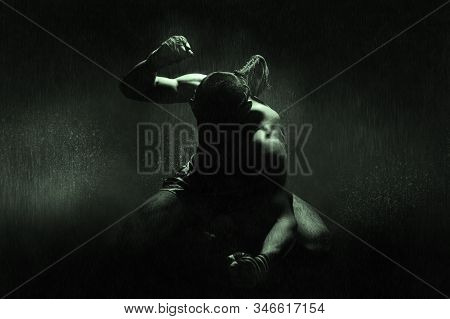 Kickboxer In The Rain And Under The Green Light Of A Spotlight. Mongkhon. The Concept Of Losing In C