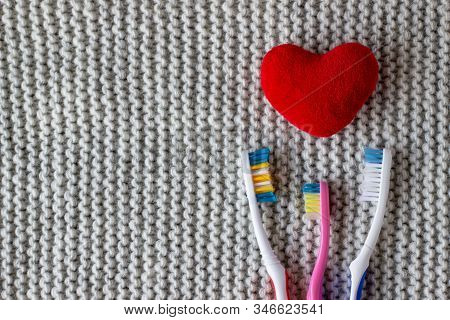 Three Toothbrushes And A Red Heart On A Knitted Gray Background. Two Adults, One Childrens Toothbrus