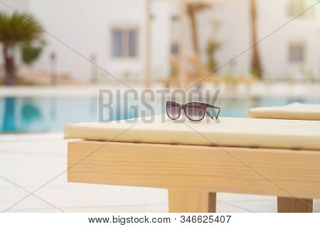 Close-up Of Woman Sunglasses On Deck Chair Near The Pool On A Bright Sunny Day. Resort Vacation Conc