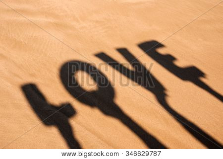 closeup of the shadow of two people holding some letters forming the word love over their heads on the sand of a beach