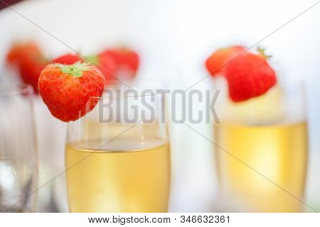 Close Up Of Glasses Of Sparkling Wine Or Champagne And Strawberry On A Blurry Background During Some