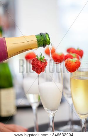 Sparkling Wine Or Champagne And Strawberry On A Blurry Background Being Poured Out From The Bottle D