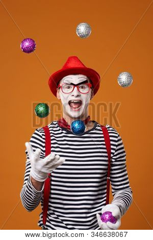 Haappy mime man in vest and red hat juggles with colorful balls on orange background
