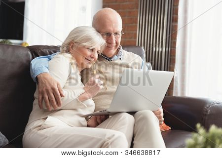 Senior Couple Browsing The Internet Together. Retirees Using A Laptop Computer At Home