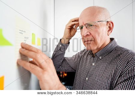 Elderly Man With Dementia Looking At Notes