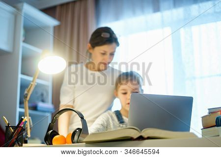 Mother Helping Teen Daughter Studying Computer While Doing Homework For School