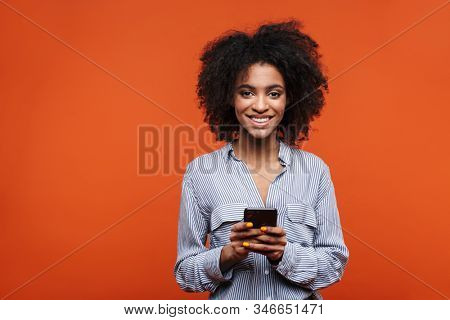 Smiling attractive young african woman using mobile phone isolated over red background