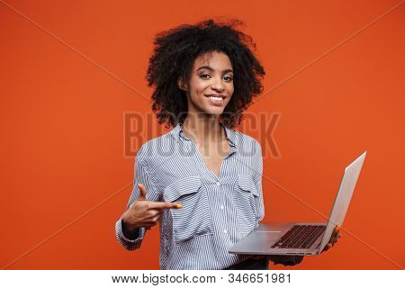 Attractive young african woman wearing casual clothes standing isolated over red background, pointing at laptop computer