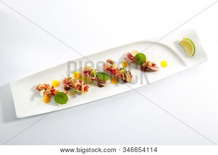 Appetizer with tuna tartar, seasonal vegetables and greens on white restaurant plate isolated. Macro photo of delicious healthy red fish tatar or tar-tar entree topview