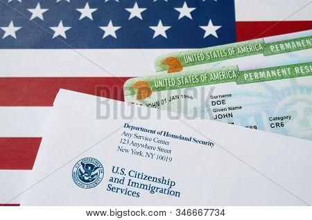 United States Permanent Resident Green Cards From Dv-lottery Lies On United States Flag With Envelop