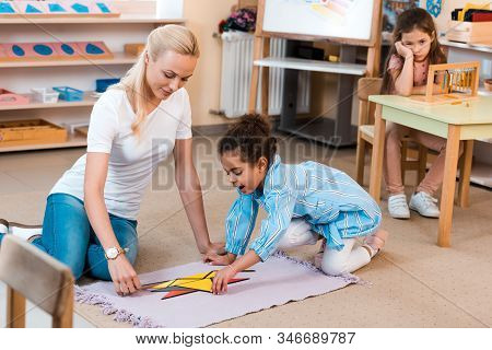 Selective Focus Of Teacher With Kid Playing On Floor And Boring Child At Desk In Montessori School