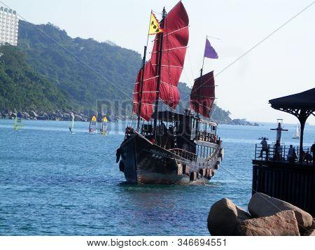Hong Kong, East Asia - November 17, 2019: Aqualuna Touring Junk Boat Leaving Pier In Small Fishing V