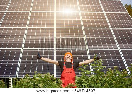 Smiling Worker With Solar Station, Raising His Hands, Showing Thumbs Up On A Background Of Photovolt