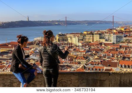 Lisbon, Portugal, January 10, 2020: Girls Tourists Admire The Panorama Of The Morning Lisbon From Th