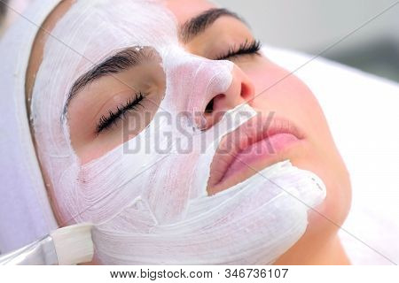 Cosmetologist Is Applying White Mask On Woman Client Face In Beauty Clinic. Portrait Of Woman Closeu