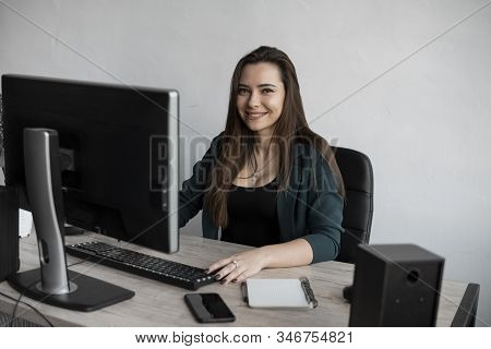 Brunette Woman Is Working In Front Of A Monitor In A Office. Business Woman Working At Computer At C