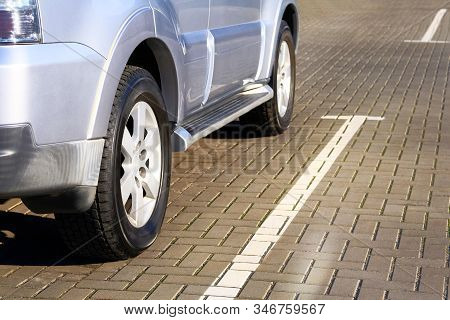Silver Car Is Parked In Its Parking Spot In City. Close Up Car Wheel, Urban Environment.