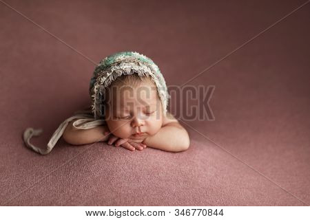 Lovely Newborn Baby Girl Laying On Her Belly. Little Girl In A Hat.