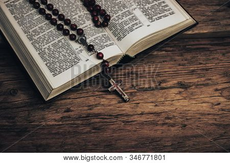Top View Open Holy Bible And Beads Crucifix On A Old Oak Wooden Table. Beautiful Red Wall Background