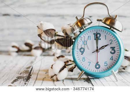 Set Your Clocks Back With This Clock Iand Bolt Of Cotton Over A White Wooden Table. Daylight Saving