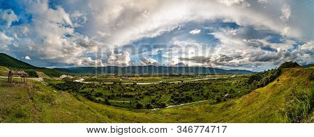 Panorama Of Lush Green River Valley At Sunset With Sun Rays And Dramatic Sky. The Area Is Known As S