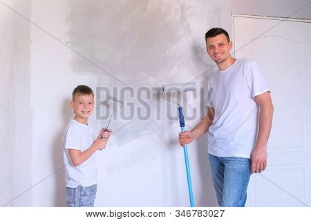 Dad And Son With Painting Rollers Are Looking At Camera And Smiling Near Wall Painted Gray. Family M