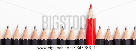 Red Pencil Standing Out From Crowd Of Plenty Identical Black Fellows On White Table. Leadership, Uni