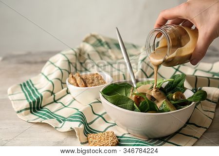 Pouring Of Tasty Tahini From Jar Onto Fresh Vegetables In Bowl