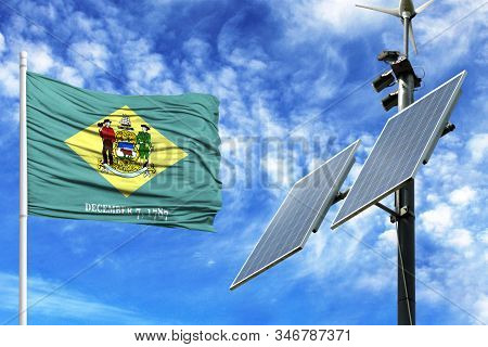 Solar Panels On A Background Of Blue Sky With A Flagpole And The Flag State Of Delaware