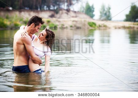 Young Beautiful Loving Couple Standing In Still Water And Looking At Each Other On Summer Day With G