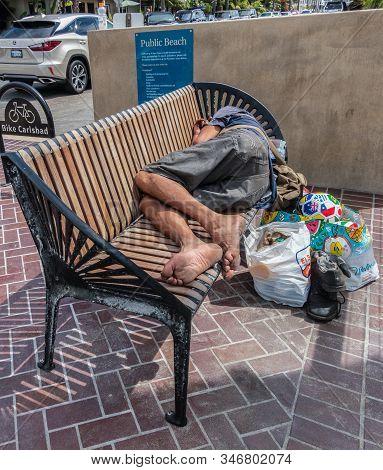 Carlsbad, California, Usa - September 22, 2019: Homeless Person Sleeps On Public Bench At Public Bea