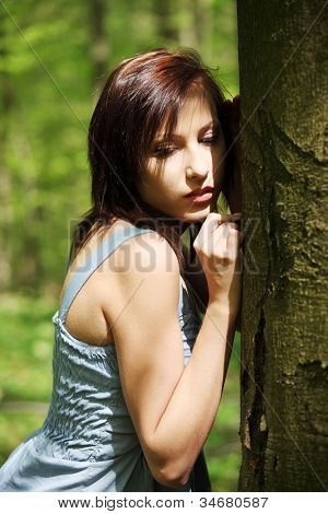Young woman holding face next to tree trying to hear voice of nature. Girl standing with ear next to wood. Pretty girl with eyes closed and summer dress.