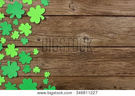 St Patricks Day Side Border Of Shamrock Decorations. Above View Over An Old Rustic Wood Background.