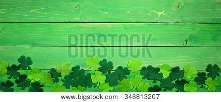 St Patricks Day Banner With Bottom Border Of Shamrocks. Overhead View Over A Green Wood Background.