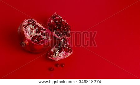 Red Pomegranate Isolated On Red Background. Pomegranate Seeds On A Red Background. Pieces Of Pomegra