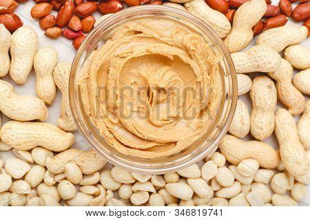 Creamy Peanut Paste, Peanut Butter In Open Glass Jar In The Center Of Peanuts Food Background. Peanu