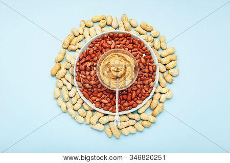 Creamy Peanut Paste In Spoon On Peanut Butter On Peanuts. Near The Peanut Butter Lies Peanuts In The