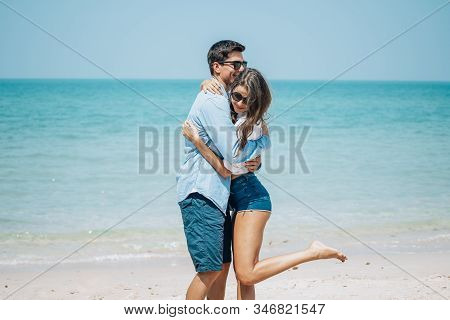 Romantic Couple Having Fun On The Beach. Happy Young Romantic Couple In Sunglasses Running On The Be
