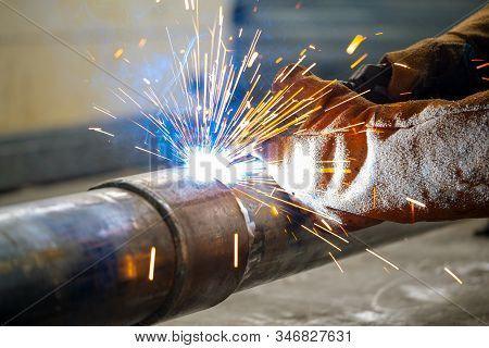 The Connection Of The Pipe With A Clamp. Welder Performs Welding Work Semi-automatic Electric Arc We