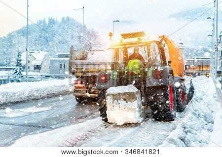 Big Tractor With Chains On Wheel Blowing Snow From City Street Into Dump Truck Body With Snowblower.