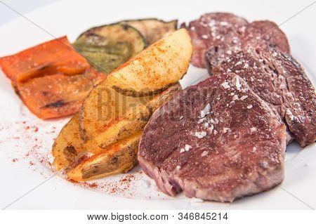 Detail Of A Beef Sirloin With Baked Potatoes And Some Vegetables Dish