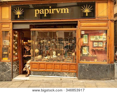 Barcelona, Spain - August 2019: Entrance And Showcase Of Souvenir Shop, Medium View. Woman Going Out