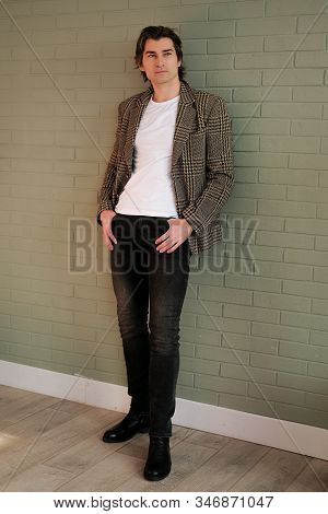 Tall Handsome Man Standing Next To Grey Wall