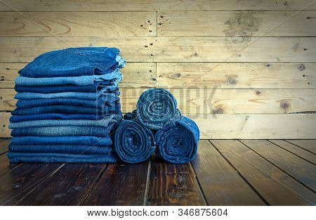 Jeans Stacked On A Wooden Background