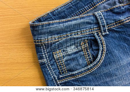 Blue Jeans On Wood Floor. Denim Texture Blank Background For Design And Text Input.