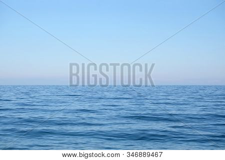 Calm Sea Surface With Small Waves In The Morning And The Land On Skyline In Light Haze In Pink And B