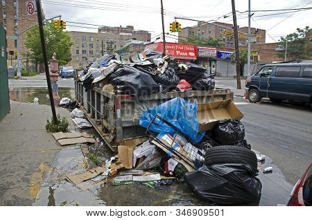 Bronx, New York/usa - July 3, 2019: Roll-off Dumpster Is Allowed To Overfill With Trash Falling Onto