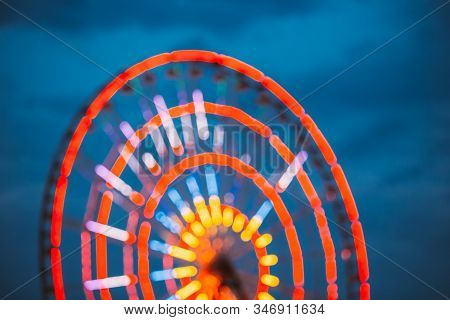 Abstract Blur Of Brightly Colorful Illuminated Ferris Wheel In Amusement City Park. Bokeh Boke Backg