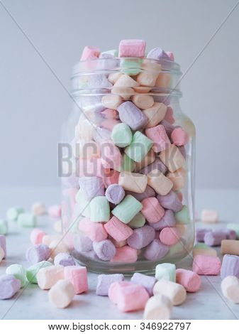 Full Glass Of Delicate Sweet Air Mini Marshmallows Scattered On The Table