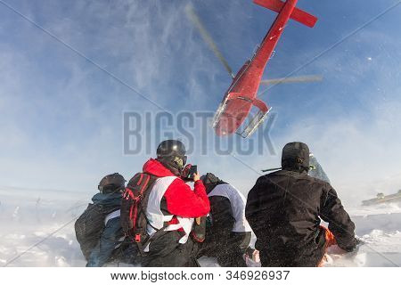 Landing From The Helicopter Skiers Freeriders In The Snowy Mountains In Winter